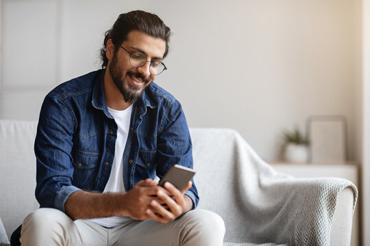 Handsome young indian guy sitting with smartphone at home, messaging with friends