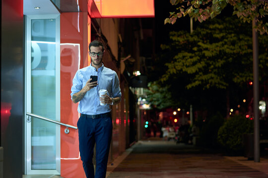 Young businessman walks with his smartphone and coffee cup at ni