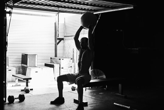 Fit young man working out with a ball and dumbells in a garage
