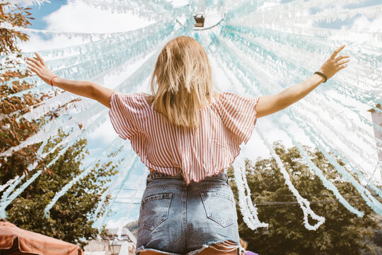 Back view of blonde woman with open arms enjoying a festival
