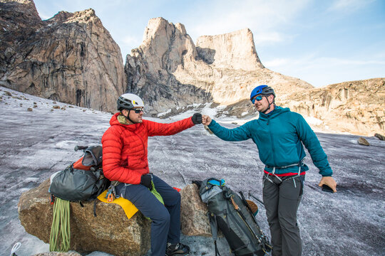 Two climbers fist bump below mountain after a successful climb