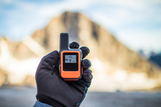 Mountaineer checks weather on small satellite communication device.