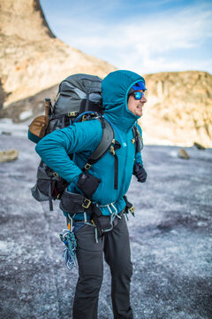 Mountain climber straps on heavy backpack during multi-day trip.