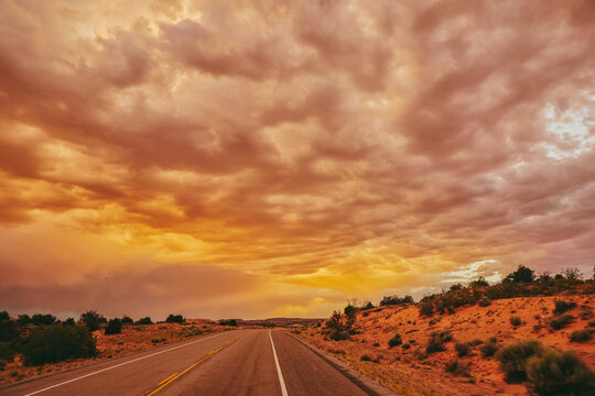 Golden sunset over storm clouds along empty highway in Moab, Utah.