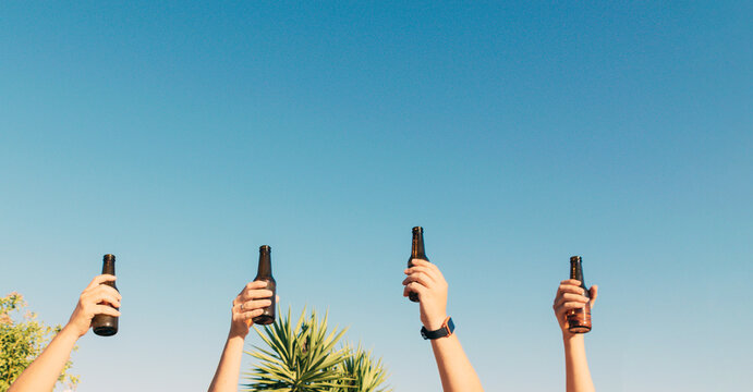 Closeup shot of bottles lifted high on blue sky background