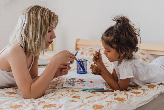 Caucasian mom and hispanic daughter painting while they are lying in the bed.