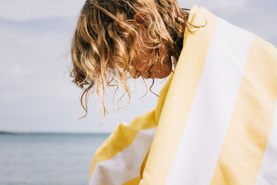 young girl with curly hair wrapped in a striped towel at the beach