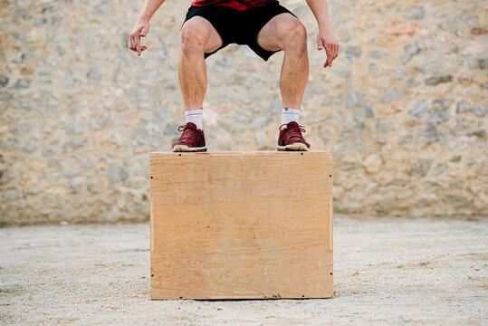 Man practicing crossfit jumping into a plyometric box.
