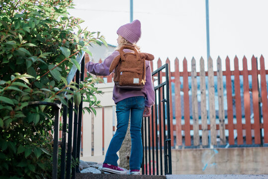 young girl stood at the top of a step looking after school thinking