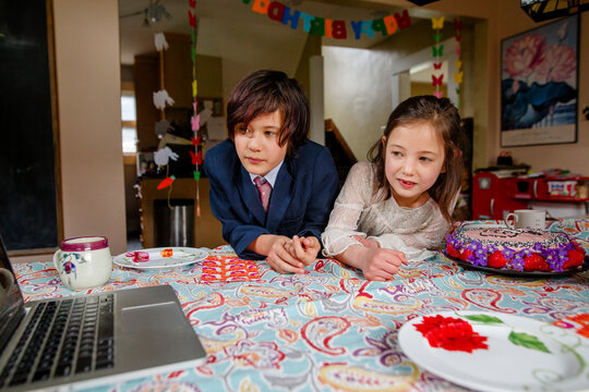 A boy and girl sit at table with birthday cake watching a computer