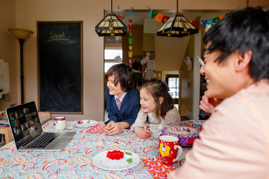 A smiling family sits at table on a zoom meeting birthday party