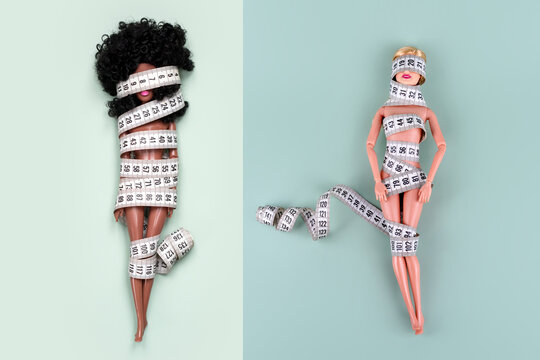 Dolls wrapped in measuring tape. Unrecognizable fashion dolls, weight loss concept. Fasting, weightloss and slimming. Diet, anorexia, eating disorder, overeating control, fight for perfect fit body.