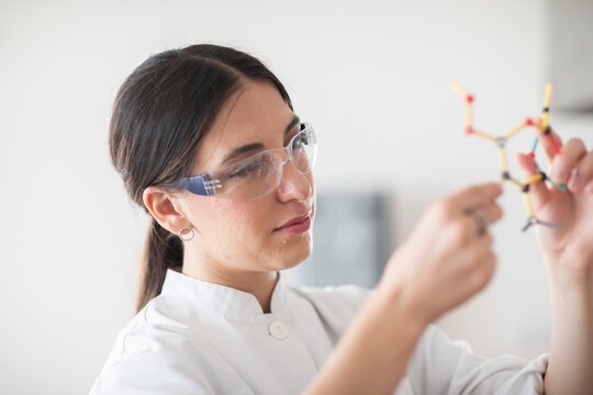 scientist female with lab glasses, tablet and sample in a lab