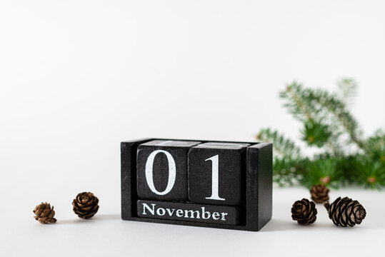 Hello November concept. Wooden calendar November 1, fir branches and spruce cones on white background. Side view, copy space. Autumn composition. Agenda, schedule, notebook background design
