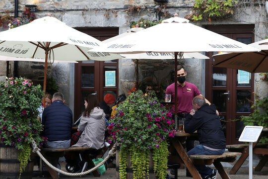 People drink outdoors in Pitlochry,  Scotland