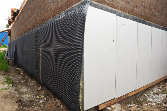 A close up on an external foundation wall of a brick house with polystyrene insulation  covered with waterproofing dimpled membrane to protect against water leaks.