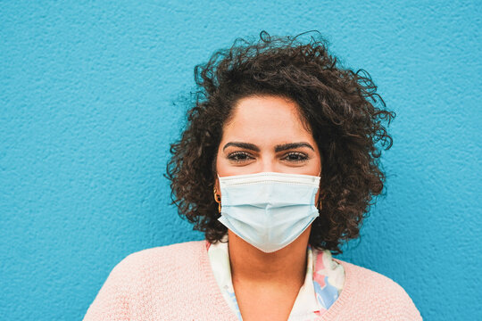 Portrait of cheerful latin woman wearing surgical face mask - Coronavirus lifestyle and health care