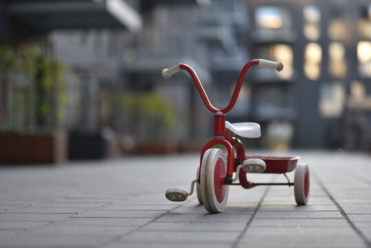 child three wheels bicycle in apartments yard