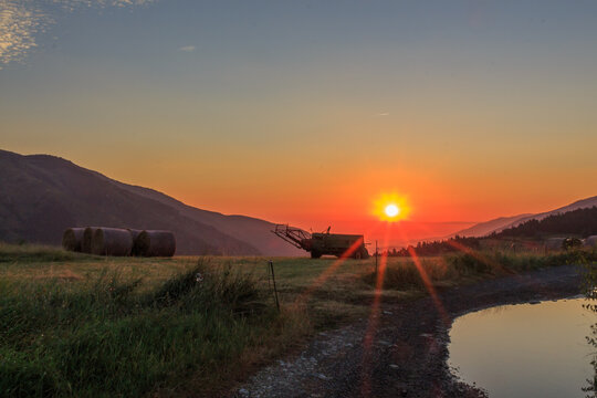 Tractor in the field with the sun rising at dawn. Field work concept