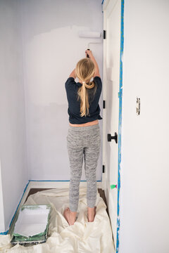 Young Girl Using Paint Roller to Paint Bedroom Wall at Home