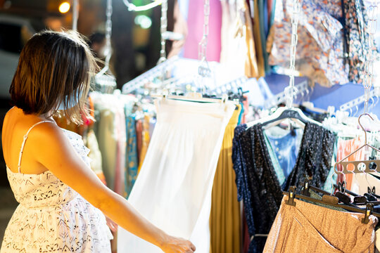 woman buying a white dress in the beach shop
