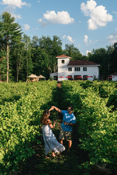 Wide shot of couple dancing in vineyard and tasting room in background
