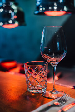 Glasses on the table in red light of infrared heat lamps in restaurant