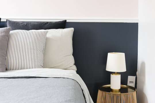 Vignette of comfortable bed in shades of blue with modern nightstand