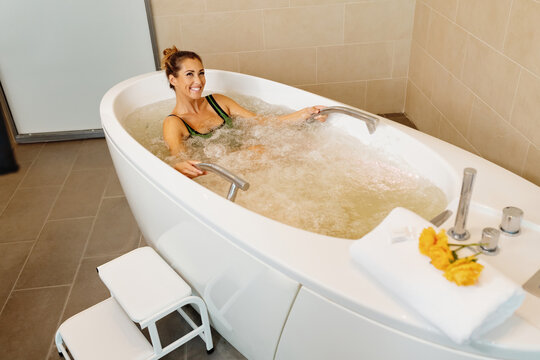 Happy woman relaxing in spa's bathtub during hydromassage treatment.