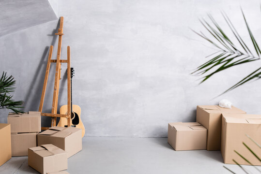 carton boxes near easel, acoustic guitar and plants