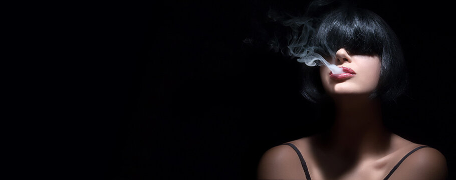 Portrait of a sensual woman with bangs vaping. Beautiful sexy woman vaping