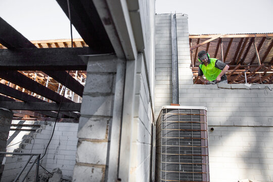 A builder working at height on a construction site.