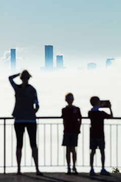 Silhouetted female and two boys standing at the viewing platform of The Summit at Mount Coot-tha.