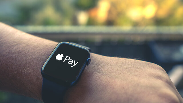 Young man using Apple Pay on a smartwatch in front of a cityscape - Apple Watch series 6 blue - Paris, France - October 10, 2020