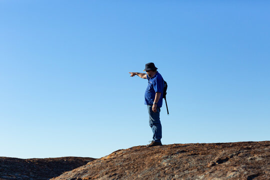 hiker on a rock pointing into the distance against a blue sky