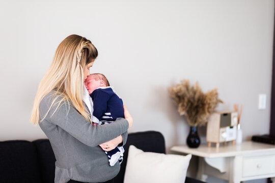 Mother holding newborn baby boy in arms cuddling