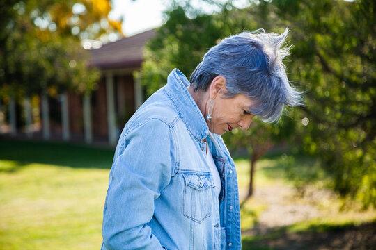 senior woman looking away strolling through garden outside
