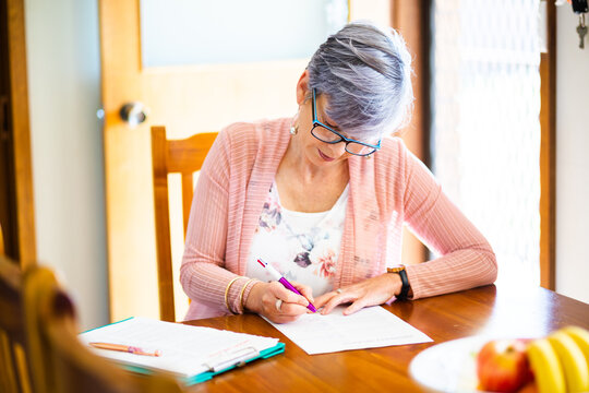 Middle aged woman signing paper documents and forms