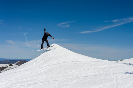 snowboarding practicing jumps in a terrain park