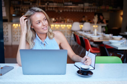 Young woman freelancing from her laptop at cafe