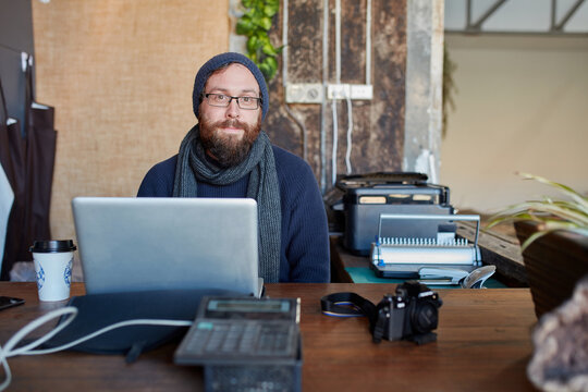 Hipster man with beanie and beard using laptop at work