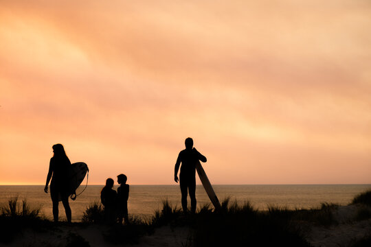 silhouette portrait of surfing family of four overlooking ocean on coastal dune holding surfboards