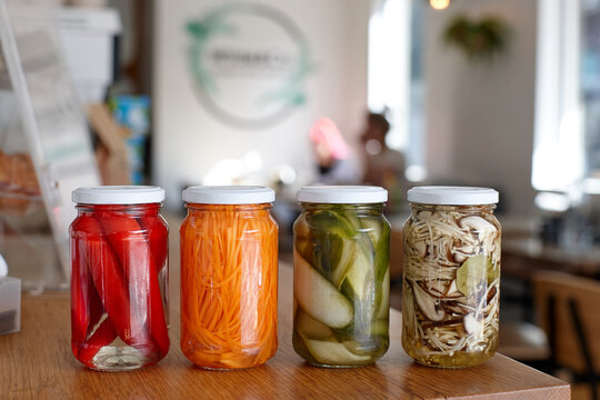 Variety of pickle jars lined up on counter in cafe