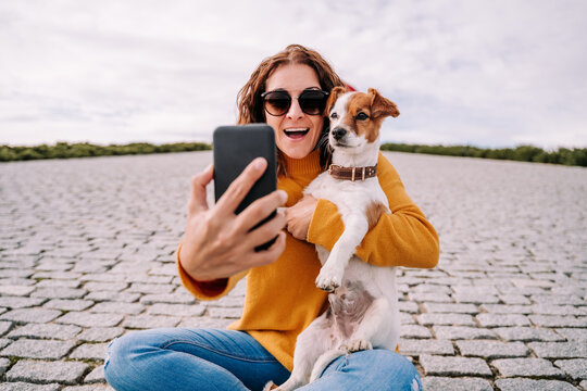A beautiful woman sitting in a park with her cute little dog. She is taking a self-portrait photo with her dog with the phone. Technology lifestyle with pets