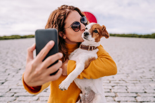 A beautiful woman staying in a park with her cute little dog. She is taking a self-portrait photo with the phone while kissing her pet. Technology lifestyle with pets