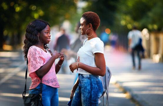 beautiful african american women talking on the crowded street