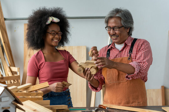 Senior Asian carpenter teaching a girl to work with wood in carpentry shop. A little African American inventor practice to be a woodworker in workshop. DIY woodworking crafts and Hobbies concepts