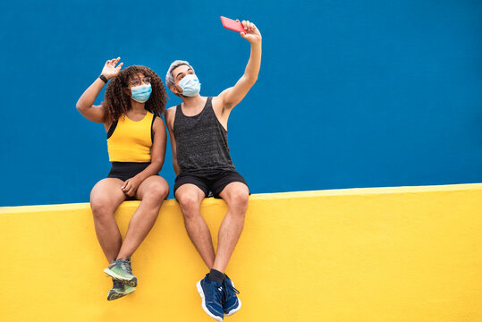 Young fitness black woman with a friend taking a selfie with mobile phone wearing face mask during coronavirus outbreak - Focus on faces