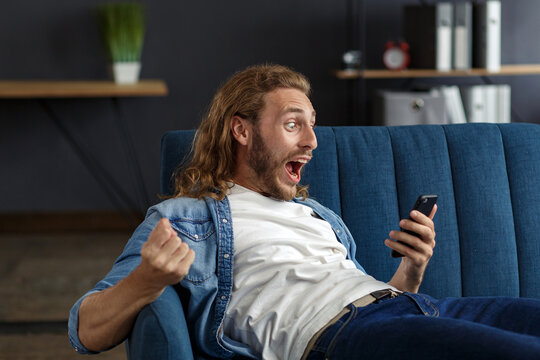 Curly-haired guy in casual style, watching great news on his mobile phone. Student receiving sms message reading good news. Surprised Man celebrating Victory on phone in Apartment.