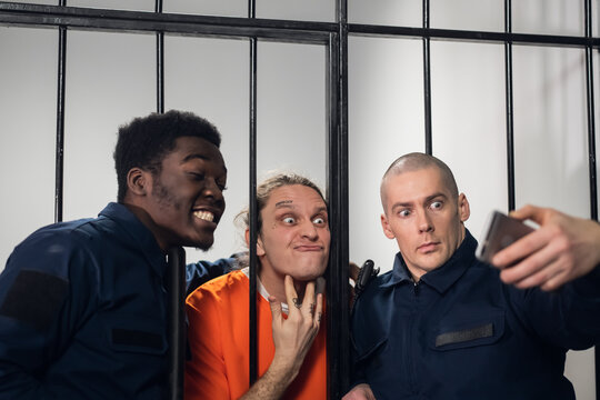 Theme party on the theme of prison. The guys take a fun selfie with each other on their smartphone